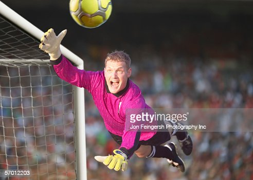 Male goalie reaching for the ball in midair : Stock Photo