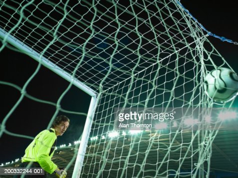 Male goalkeeper watching ball bulging in back of net