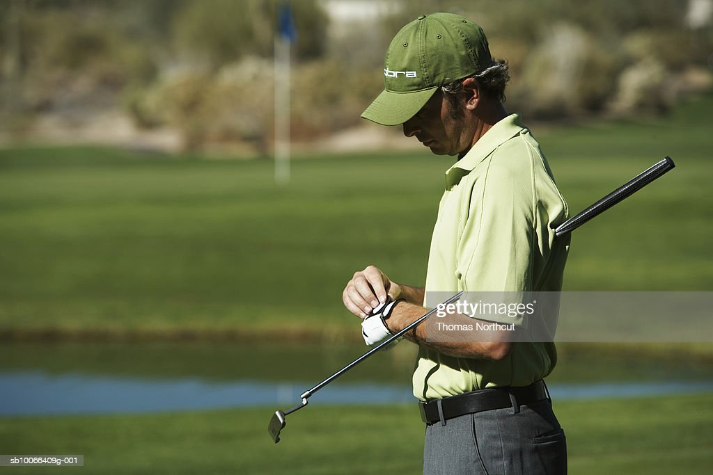 Male golfer adjusting gloves on golf course : Stock Photo