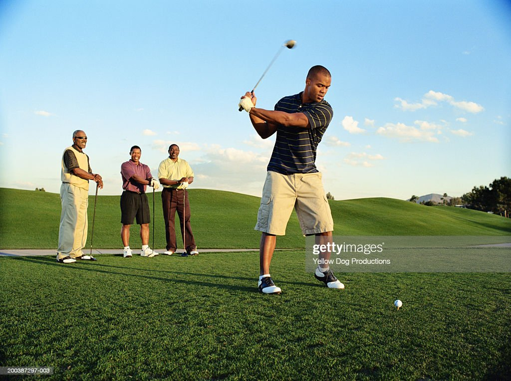 Male golfer driving ball, friends watching (blurred motion) : Stock Photo