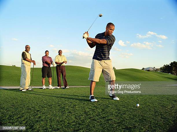 Male golfer driving ball, friends watching (blurred motion)