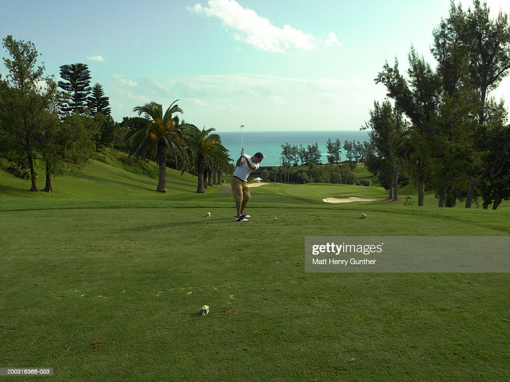 Male golfer driving golf ball, side view : Stock Photo