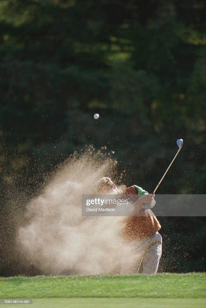 Male golfer hitting out of a sand trap onto the green