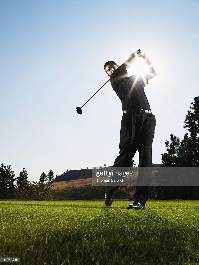 Male golfer hitting tee shot : Stock Photo