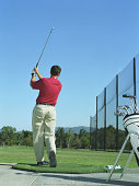 Male golfer in mid swing on driving range, rear view