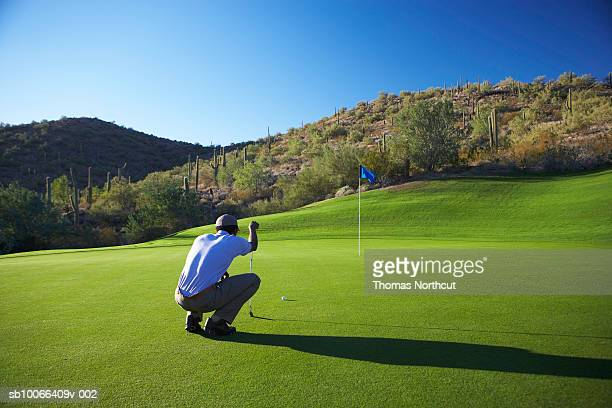 Male golfer lining up putt on golf course