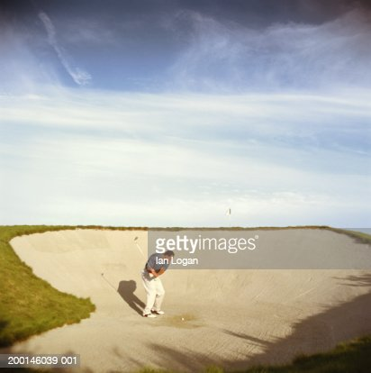 Male golfer playing in sand trap
