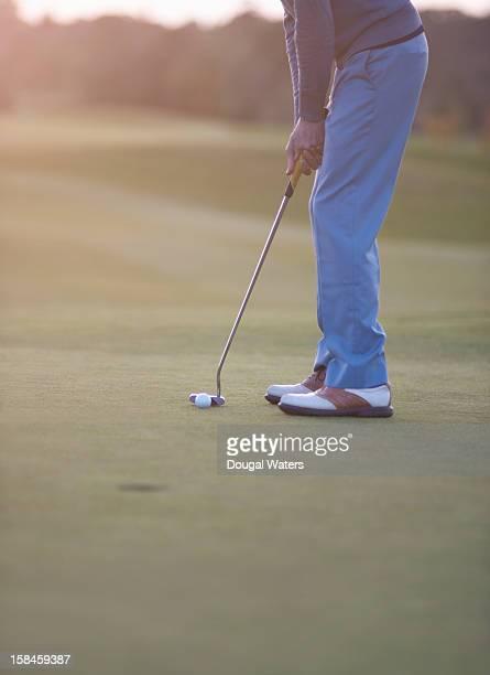Male golfer preparing to putt ball on green.