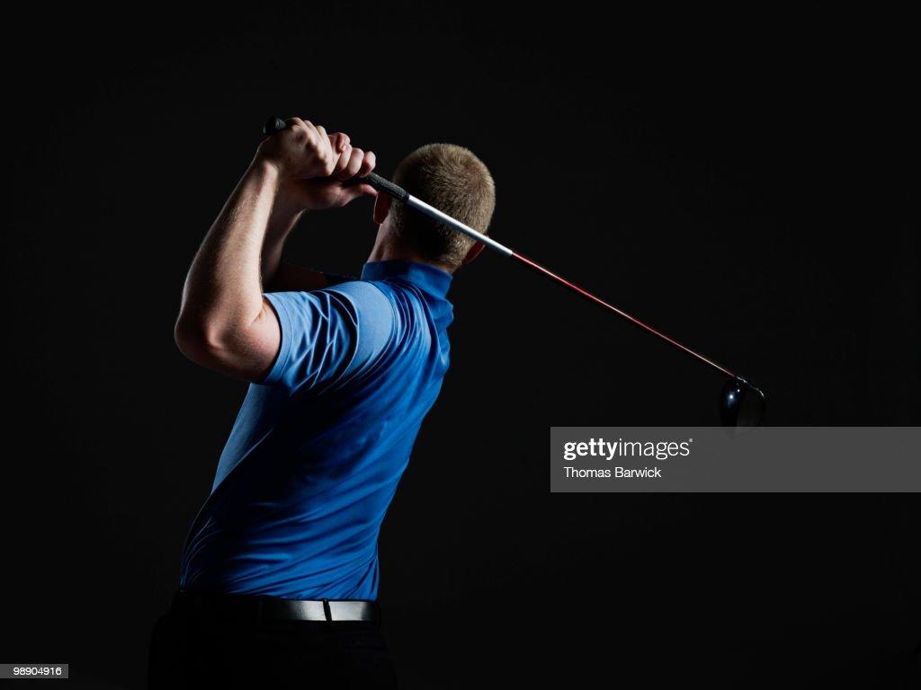 Male golfer swinging club rear view : Stock Photo