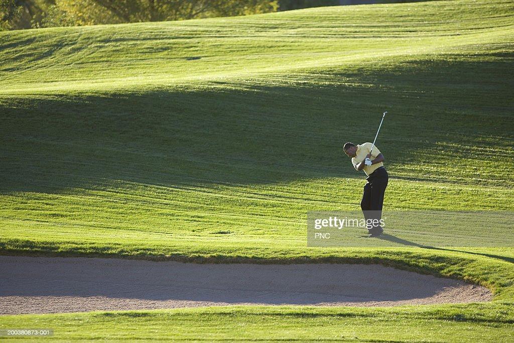 Male golfer swinging golf club beside sand trap, side view