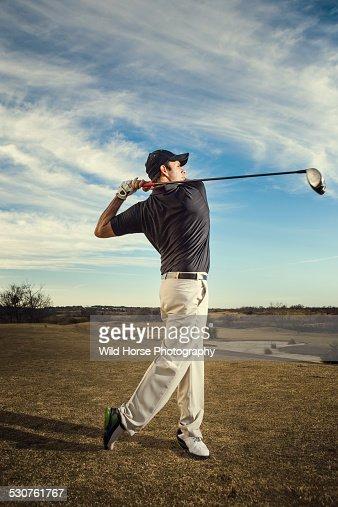 A male golfer swinging golf club