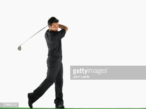 Male golfer swinging golf club : Stock Photo
