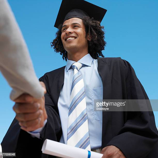 Male graduate student receiving diploma from dean, outdoors