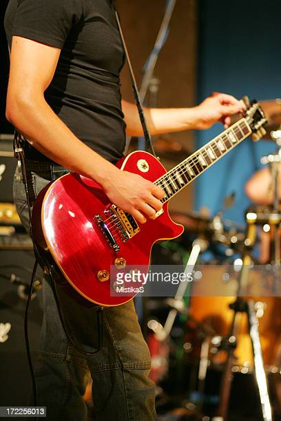 Male guitarist tuning his guitar