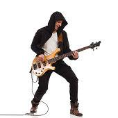 Shouting guitarist in black hoodie play the bass guitar. Full length studio shot isolated on white.