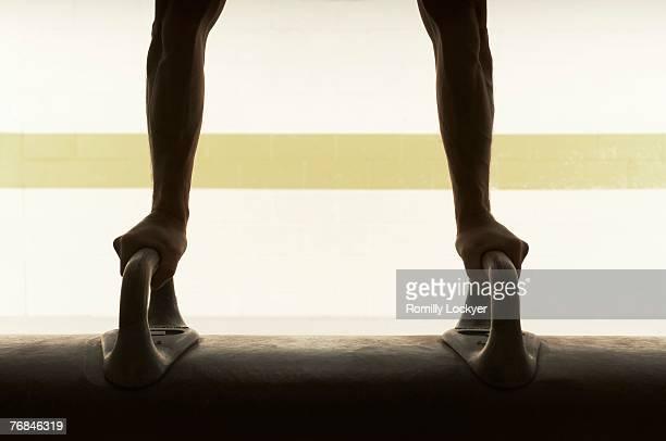 Male gymnast balancing upside down on pommel horse