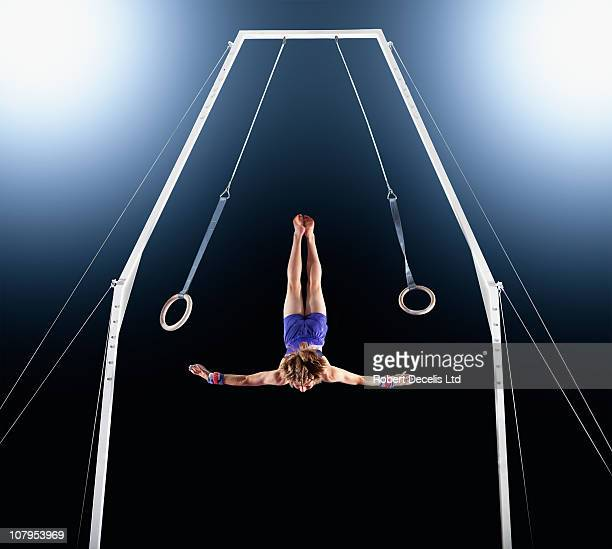 Male gymnast dismounting from rings