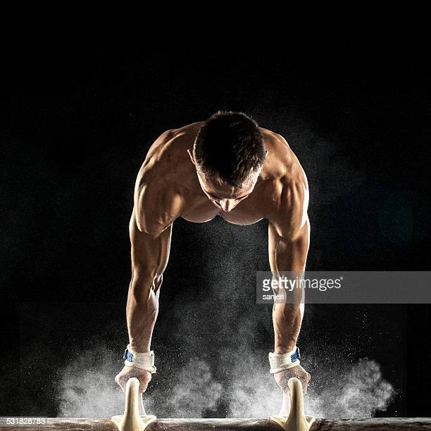 Male Gymnast doing handstand on Pommel Horse