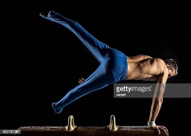 Homme gymnaste en équilibre sur les mains sur un Cheval-d'arçons