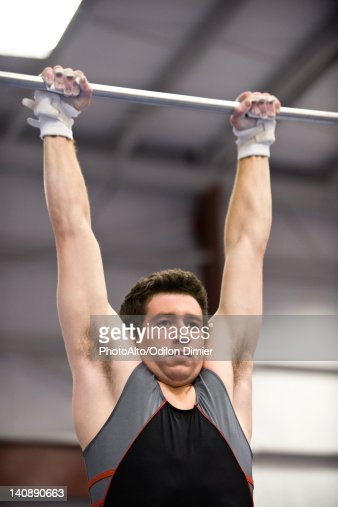 Male Gymnast Hanging From Horizontal Bar Stock Photo