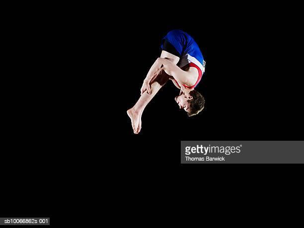 Male gymnast (16-17) mid air, black background