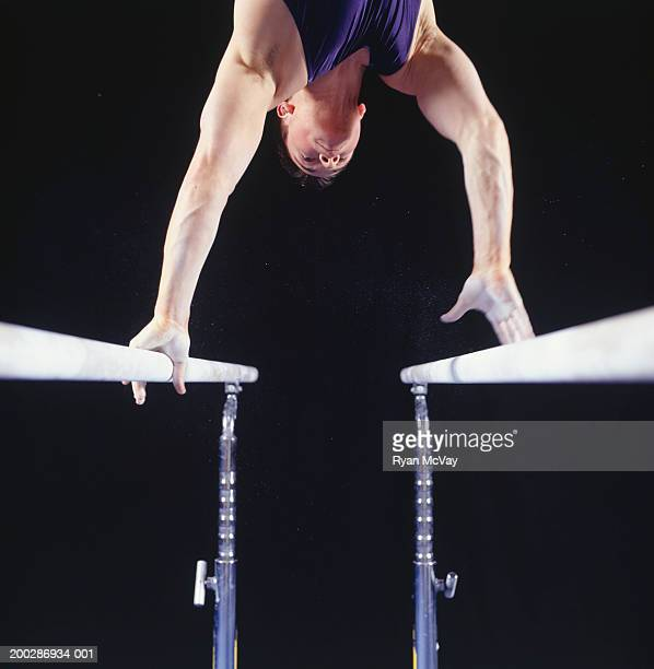 Male gymnast on parallel bars, low angle view