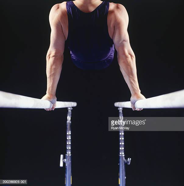 Male gymnast on parallel bars, rear view
