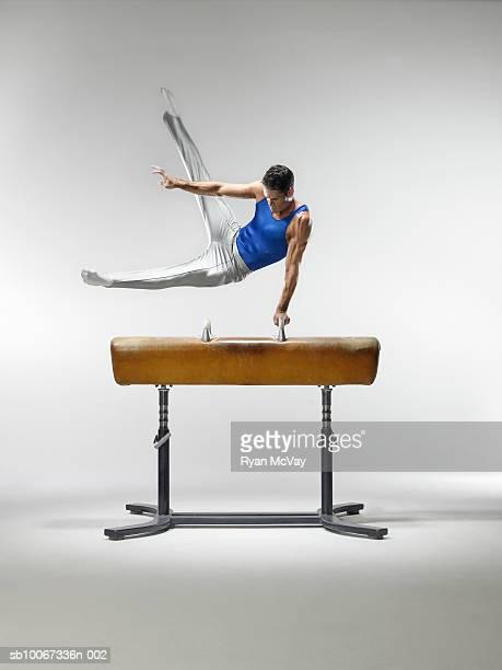Male gymnast on pommel horse, studio shot