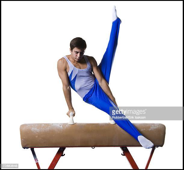 Male gymnast performing routines on vaulting horse