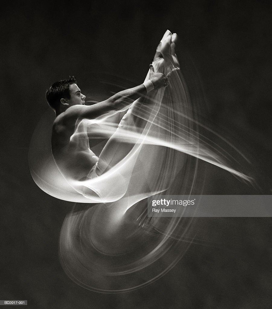 Male gymnast performing somersault (blurred motion, B&W)