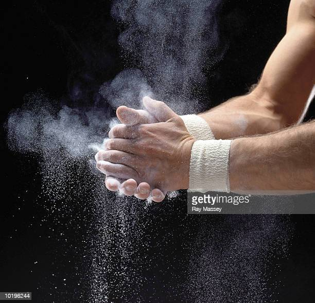 Male gymnast powdering hands, close-up
