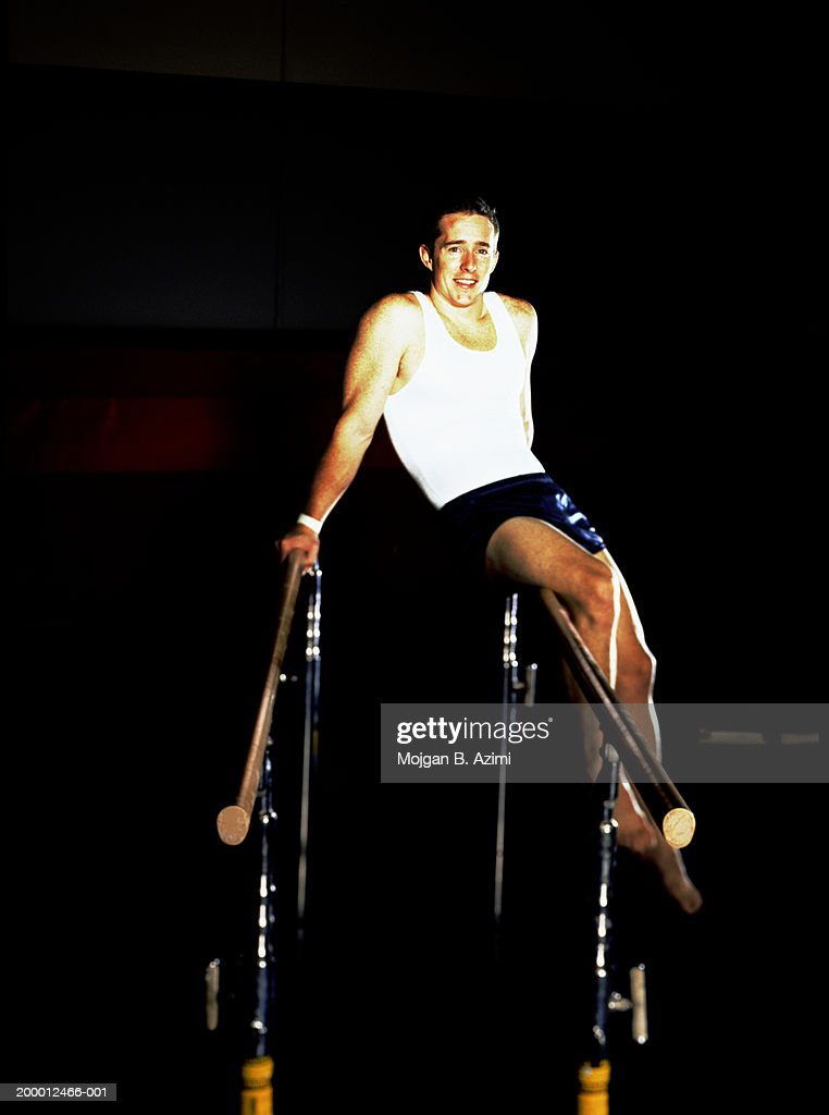 Male gymnast sitting on parallel bars