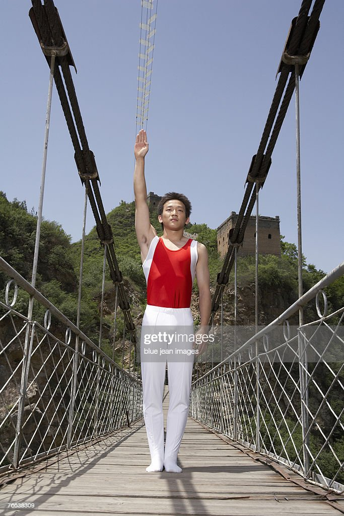 A male gymnast standing on a hanging bridge at the Great Wall of China. : Stock Photo
