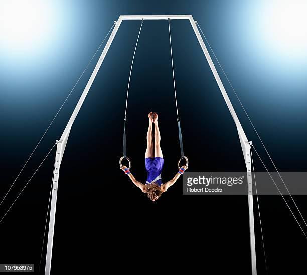 Male gymnast upside down performing on rings