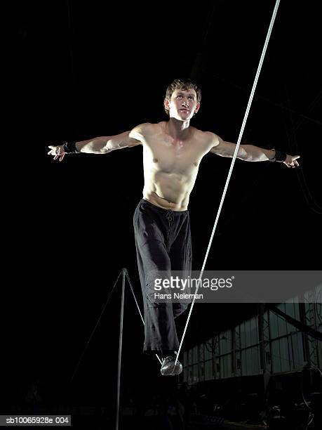 Male gymnast (16-17) walking on tightrope, low angle view