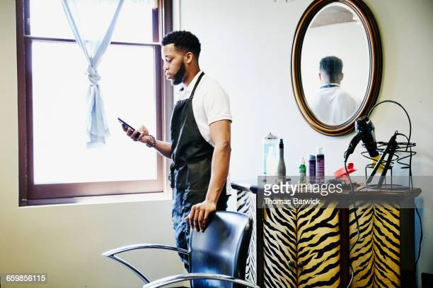 Male hair stylist in salon checking smartphone
