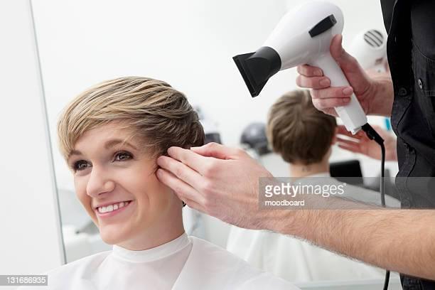 Maschio parrucchiere asciugatura capelli del cliente
