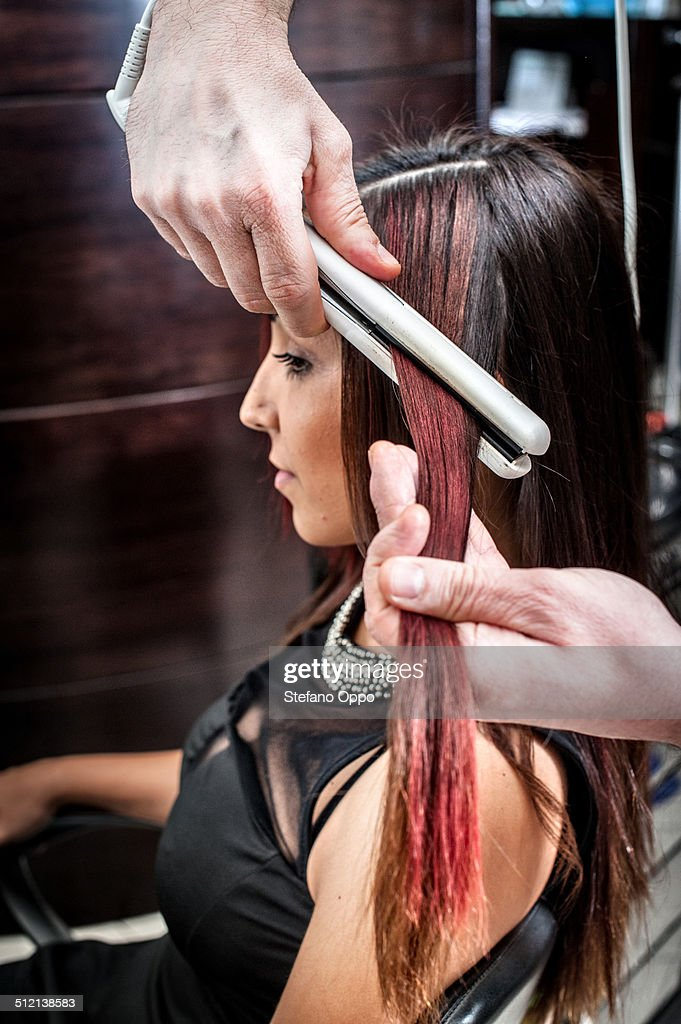 Male hairdresser straightening young woman's hair in hair salon