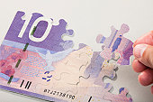 Male hand arranging Puzzle Pieces creating canadian currency