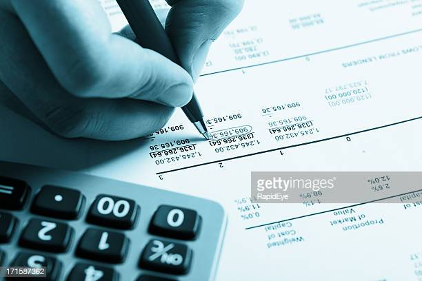 Male hand circles a figure on financial document with ballpoint