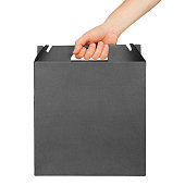 Male hand holding black cardboard box with handle isolated on white background. Delivery mockup