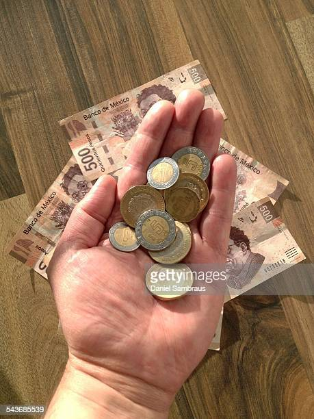 A male hand holding Mexican pesos coins above peso banknotes
