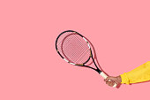 Close-up view of male hand holding tennis racket on pink background