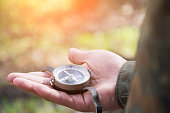 male hand holds a magnetic compass, forest hike
