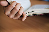 Male hand holds the opened book. View of the book back close-up.