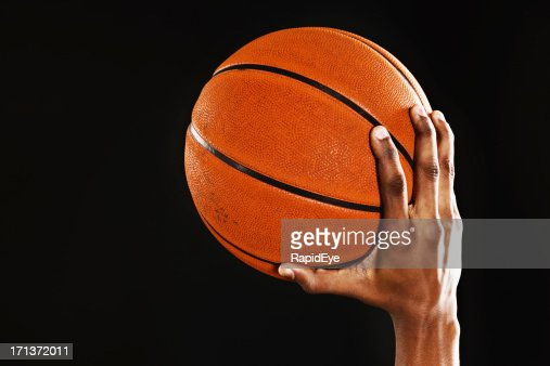 Male hand holds up a basketball ready to shoot : Stock Photo