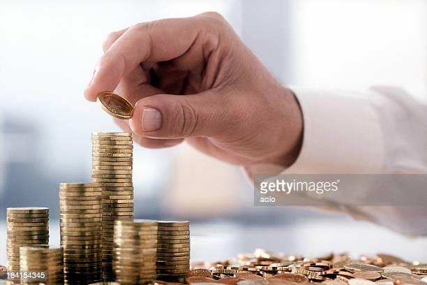 Männlichen hand Stapeln von Münzen