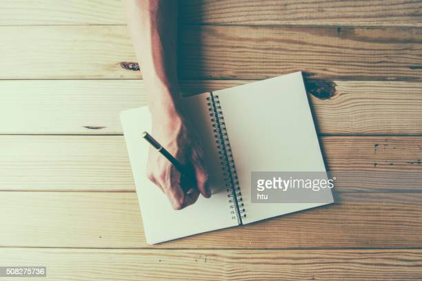 male hand is writing in a big notepad on a wooden table