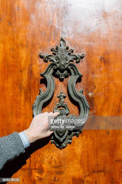 Male hand knocking on the old door with a door knocker