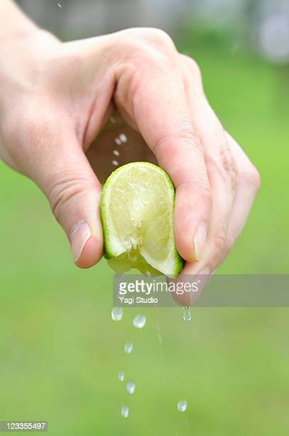 Male hand squeeze the lime